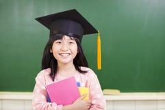 Le flickan bär en avläggande av examenhatt Royaltyfri Bild