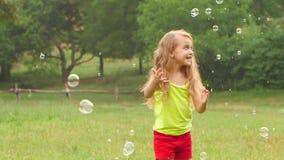 Le flickan ha roliga spela låssåpbubblor i sommar att parkera långsam rörelse stock video