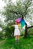 Le flickan i den vita klänningen och regnbåge-kängor som står i den blommande trädgården med det färgrika regnbåge-paraplyet Royaltyfri Bild