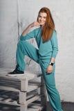 Le flickan i overaller som står på paletter Royaltyfri Bild
