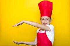Le flickan i röda en kocks dräktpunkter med båda händer till ett kopieringsutrymme på en gul bakgrund royaltyfria foton