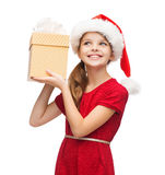 Le flickan i santa hjälpredahatt med gåvaasken arkivbilder