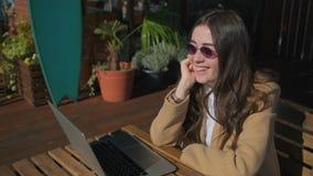 Le flickan i stilfull kläder med en bärbar dator arkivfilmer