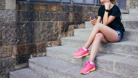 Le flickan iklädda svarta T-shir, kortsluter kort grov bomullstvill och rosa gymnastikskor som sitter på stenmoment och använder  Arkivfoto