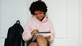 Le flickan med böcker och digitalt minnestavlasammanträde på väggen royaltyfria foton