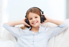 Le flickan med hörlurar som lyssnar till musik Arkivfoton