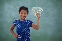 Le flickan med handen på höften som visar pappers- valuta Arkivbild