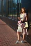Le flickan med shoppingpåsar med telefonen i hand Royaltyfri Foto