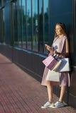 Le flickan med shoppingpåsar med telefonen i hand shoppare försäljningar Begrepp av kvinnashopping Royaltyfri Foto
