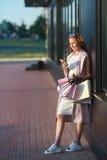 Le flickan med shoppingpåsar och se i telefonen Arkivfoto