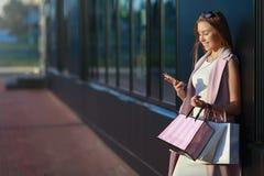 Le flickan med shoppingpåsar och se i telefonen Arkivfoton