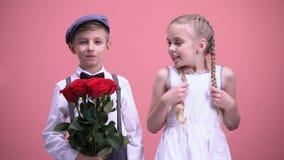 Le flickan och hennes lilla pojkvän som rymmer röda blommor som ser till kameran lager videofilmer