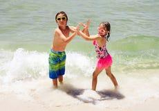 Le flickan och pojken som tillsammans dansar i vatten Arkivbilder