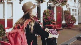 Le flickan rider en cykel med en röd ryggsäck Ultrarapidnärbild Europeiska kvinnaritter längs gatan med blommor lager videofilmer