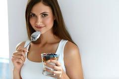 Le flickan som äter sund organisk yoghurt med bär och havre arkivfoto