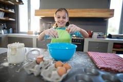 Le flickan som bryter ägget arkivfoton