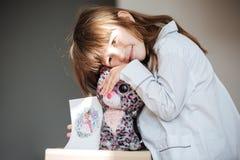 Le flickan som kramar leksaken och uppvisning av vykortet Arkivbilder