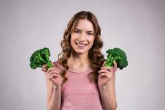 Le flickan som poserar med broccoli fotografering för bildbyråer