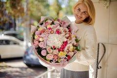 Le flickan som rymmer en härlig bukett av olika rosa blommor royaltyfria foton