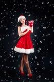 Le flickan som rymmer röda bollar för en julgran Kvinnor på klänningen och hatten för santa ` s hjälpreda s santa Attraktiv lyckl Fotografering för Bildbyråer