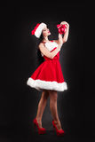 Le flickan som rymmer röda bollar för en julgran Kvinnor på klänningen och hatten för santa ` s hjälpreda s santa Attraktiv lyckl Royaltyfri Bild