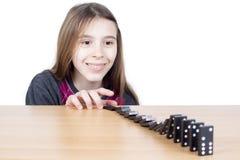 Le flickan som ser svart domino som ner faller på träbrädet som isoleras på vit bakgrund Royaltyfria Bilder