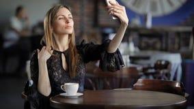 Le flickan som tar selfie Ungt le kvinnligt smaklöst klänningsammanträde på tabellen i kafé och taselfie arkivfilmer