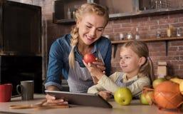 Le flickan som visar ett äpple till hennes moder Royaltyfri Bild