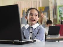 Le flickasammanträde vid bärbara datorn i klassrum arkivfoton