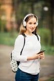 Le flickastudenten som är utomhus- med påsen och anteckningsboken nära universitet royaltyfri foto