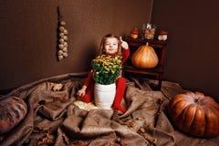 Le flickavisningtummen upp sammanträde med vasen av blommor Royaltyfri Foto