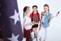 Le flickor med amerikanska flaggan som talar och dricker drycker som isoleras på vit royaltyfri fotografi