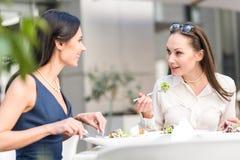 Le flickor som äter sallad på skrivbordet Arkivfoto