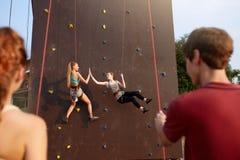 Le flickor som ger höjdpunkt fem som hänger på rep på den konstgjorda klättringutbildningsväggen och som försäkrar av vänner på s royaltyfria bilder