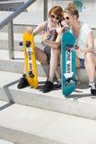 Le flickor som sitter med skateboarder royaltyfria bilder
