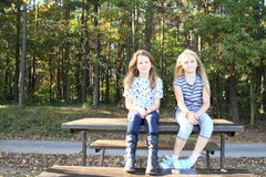 Le flickor som sitter på tabellen Arkivbilder