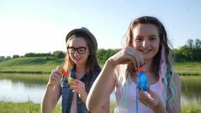 Le flickväntonåringar som blåser såpbubblor på naturen på solig sommardag arkivfilmer