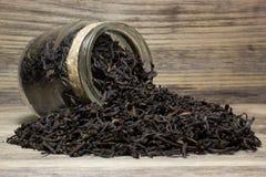 Le foglie di tè asciutte per tè nero e vetro stonano Immagine Stock