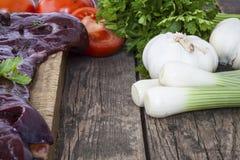 Le foie avec des légumes a tiré sur un fond en bois Images stock