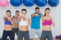 Le folk som gör maktkonditionövning på yogagrupp Royaltyfria Bilder