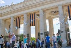 Le folle della gente entrano e lasciano nel parco di Gorkij dai portoni dell'entrata principale Fotografia Stock Libera da Diritti