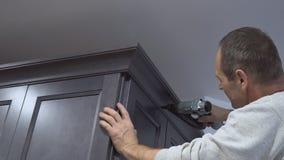 Le fonctionnement de bricoleur installent l'arme à feu de clou de pointe pour couronner les coffrets de mur de moulage encadrant  clips vidéos