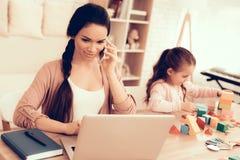 Le fonctionnement de femme sur l'ordinateur portable et la fille jouent les cubes futés photo stock