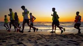 Le fonctionnement de formation d'équipe de football extérieur sous le coucher du soleil de plage Photos stock