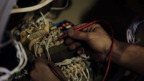 Le fonctionnement de l'usine avec un multimètre mesure la tension dans l'unité de connecteur banque de vidéos