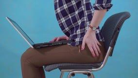 Le fonctionnement se reposant de femme sur un ordinateur portable éprouve la douleur et le malaise des hémorroïdes se ferment  banque de vidéos