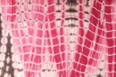 Le fond abstrait de rouge, de blanc, et le rose teignent en nouant le tissu Photo stock