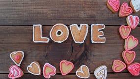 Le fond avec la forme de coeur et le mot aiment les biscuits faits maison de valentine Photos stock