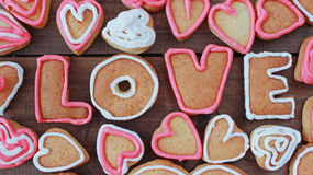 Le fond avec la forme de coeur et le mot aiment les biscuits faits maison de valentine Photographie stock libre de droits