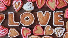 Le fond avec la forme de coeur et le mot aiment les biscuits faits maison de valentine Photo libre de droits